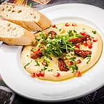 Hummus podawany z granatem, rukolą, suszonymi pomidorami, pietruszką,oliwą i pieczywem