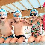 Zadowolone dzieci na pływalni podczas lekcji pływania z instruktorem w miejscu: Basen Gdańsk Osowa