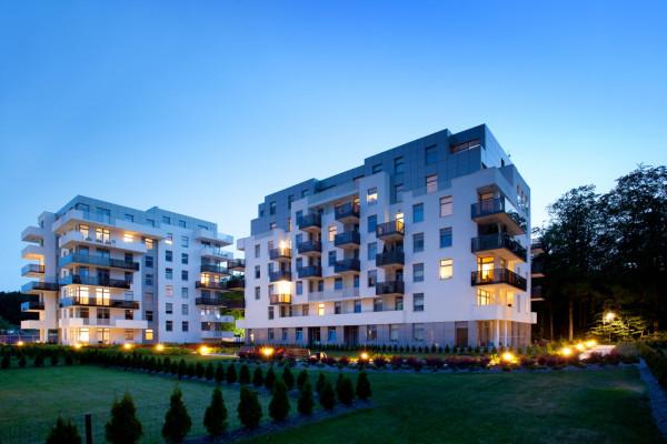 Białe, nowoczesne elewacje otoczone zielenią podkreślają elegancję i klasę budynków.