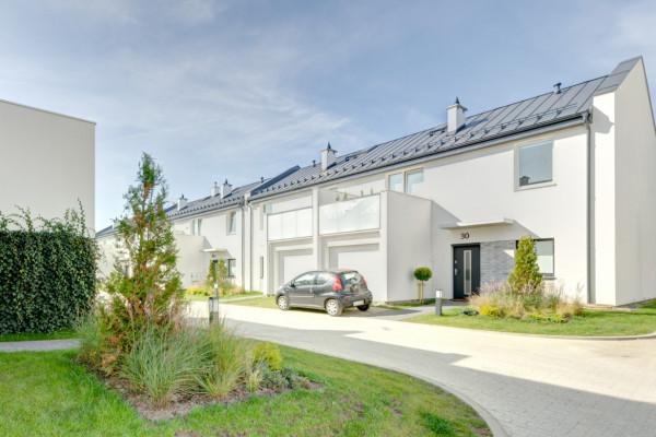Osiedle niewielkich białych domów otoczonych zielenią robi wrażenie przytulnego zakątka.