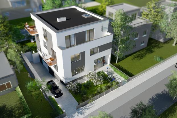 Budynek powstaje na zielonej działce, wśród niewysokiej zabudowy.
