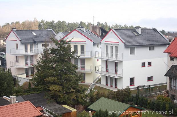 Budynki tworzą kameralny kompleks otoczony zielenią.