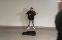 Skrzypek gra kolędy w tunelu w Gdańsku Głównym