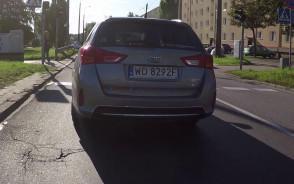 Samochód spycha rowerzystę