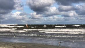 Windsurfer korzysta z silnego wiatru na zatoce