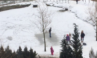 Dzieci ślizgają się na lodzie na oczku wodnym