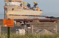 Refulacja plaży na Helu, robotnicy szukają bursztynów