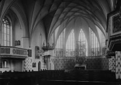 Wnętrze kościoła z czasów ewangelickich. Przy ścianach widoczne są drewniane empory, a w prezbiterium ołtarz w kształcie Drzewa Życia.