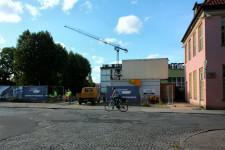 Inwestycja otoczona jest z lewej strony Parkiem Kuźniczki, z prawej Dworem Kuźniczki, zaś z tyłu widać powstający budynek na terenie dawnego browaru.