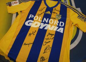Arka Gdynia pośród licznych gadżetów klubowych na licytację przekazała m.in. meczowy trykot z podpisami zawodników.