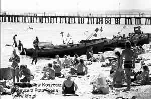 Plażowicze, kutry rybackie i molo w Orłowie. Zdjęcie wykonane w połowie lat 70. XX wieku.