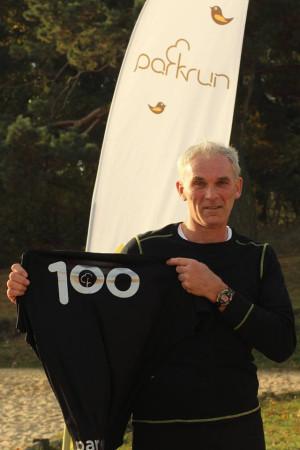 Jerzy Krzak z koszulką techniczną za udział w 100 biegach.