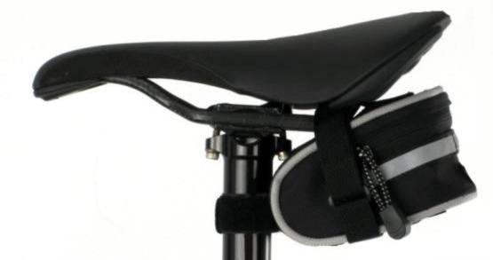 Standardowa torebka podsiodłowa mocowana za pomocą opaski na rzep opasającej rurę siodła oraz paska na klamrę zakładanego między pręty siodełka.