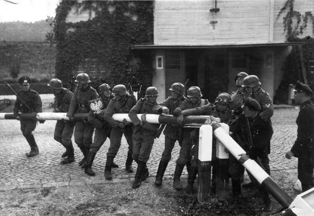 """Policjanci gdańscy łamiący szlaban na przejściu granicznym w Kolibkach, między Wolnym Miastem Gdańskiem a Polską. Propagandowe zdjęcie wykonano 1 września w porannych godzinach (ukazało się w weekendowym wydaniu """"Danziger Vorposten"""" 2/3 września 1939 r.). Tymczasem w nocy z 1 na 2 września oddziały polskie przyprowadziły kontratak, wypierając napastników z zajętych pozycji."""