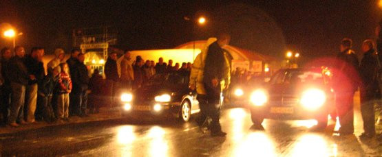 Ściagające się auta ruszają na znak dany przez mężczyznę kierującego zaimprowizowanym startem.