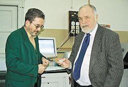 Naklejka jest wielkości znaczka pocztowego - pokazuje prof. dr hab. inż. Wacław Grzybkowski. Z lewej stoi dr hab. inż. Wojciech Chrzanowski.