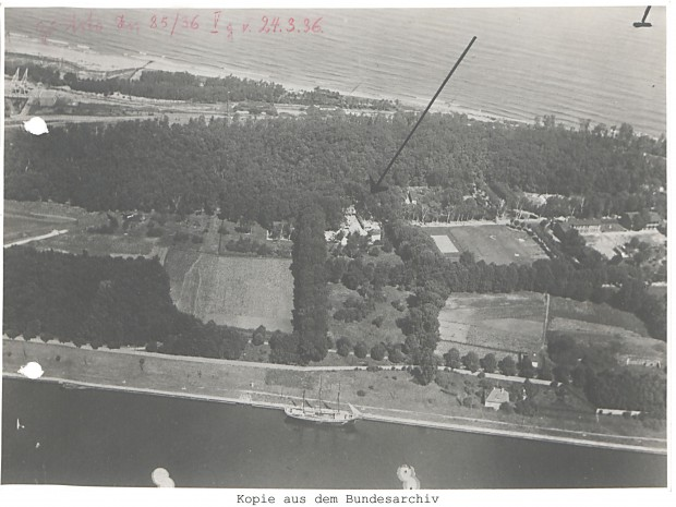 Fotografia lotnicza Westerplatte, strzałką zaznaczono wznoszony budynek Nowych Koszar.
