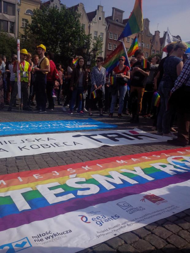 Wśród uczestników Marszu Równości dominują tęczowe flagi oraz transparenty nawołujące do tolerancji dla osób homoseksualnych.