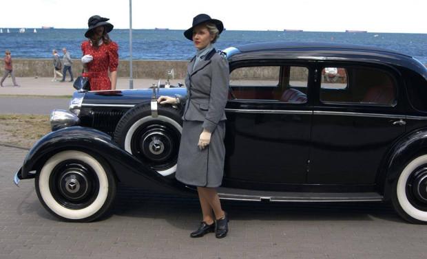 Mercedes w towarzystwie pań odzianych w stroje z epoki.
