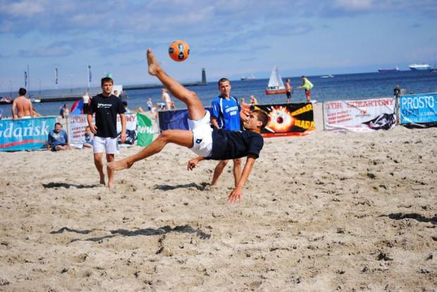 Piłka nożna plażowa to niezwykle efektowny sport, ale jego uprawianie wymaga sporej sprawności fizycznej. W te wakacje na trójmiejskich plażach będzie można podszkolić swoje umiejętności m. in. strzelania przewrotką.