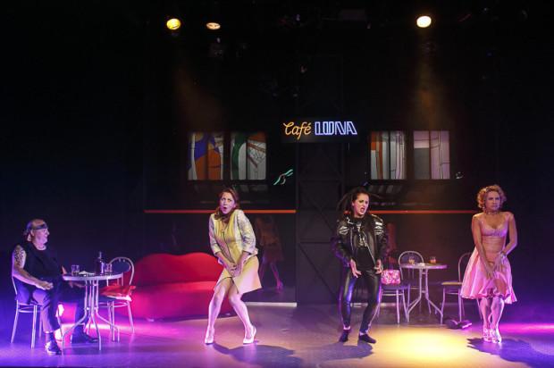 """Na potrzeby spektaklu foyer Teatru Miejskiego zamieniło się w knajpkę """"Cafè Luna"""", w której trzy samotne kobiety pod okiem zmęczonego barmana (Maciej Sykała) prowadzą niekończące się rozmowy o mężczyznach swoich marzeń."""