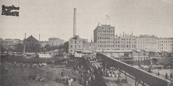 """Zdjęcie młyna olejowego. Widać na nim dodatkowy równoległy do Mostu Toruńskiego most prowadzący do olejarni - ułatwiał transport przez nową Motławę produktów olejarni i nie tylko. Zdjęcie zamieszczone przez Jacka Górskiego w artykule na temat historii Fabryki Batycki na stronie opowiadaczehistorii.pl, pochodzi z książki """"Danzig und seine Bauten"""" z 1908 roku, str. 375."""