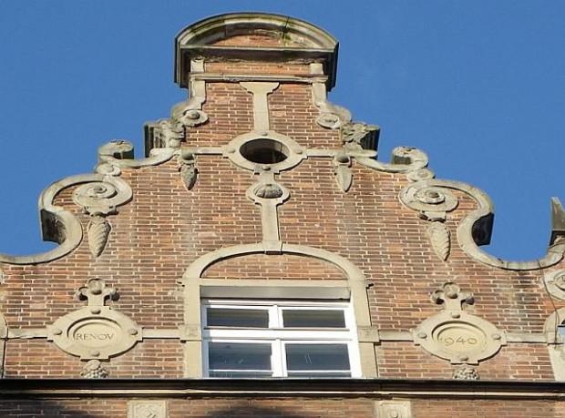 Szczyt kamienicy przy ul. Garbary 1 w Gdańsku z datą renowacji budynku umieszczoną w dwóch medalionach na fasadzie.