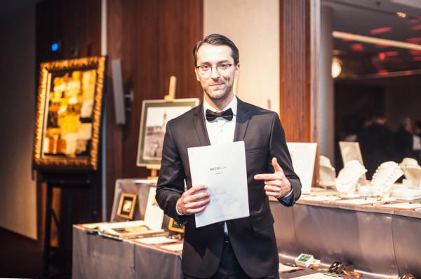 """Aktor Filip Bobek - tegoroczny gość honorowy balu - ze scenariuszem serialu """"BrzydUla"""", który przekazał na licytację."""