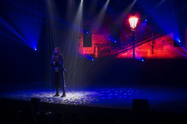 """Oprawę wizualną koncertu stanowi ekran projekcyjny i umiejętnie ustawione światła. Na zdjęciu Agnieszka Piech w bardzo dojrzale zinterpretowanej piosence """"Sama wciąż"""" z musicalu """"Les Misérables""""."""