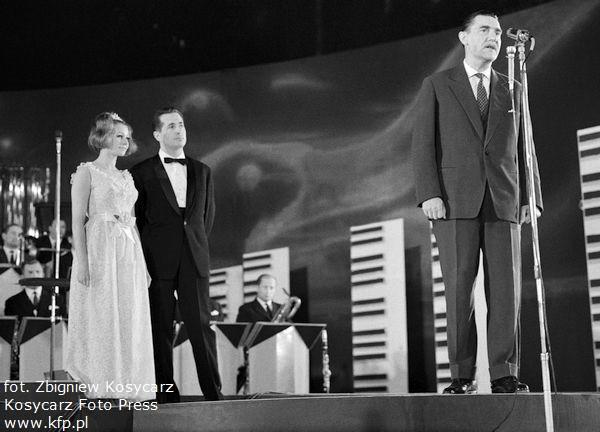 IV Międzynarodowy Festiwal Piosenki w Sopocie w 1964 r. Na scenie przy mikrofonie Stanisław Podraszko, przewodniczący Miejskiej Rady Narodowej. Za nim Krystyna Loska i Lucjan Kydryński.