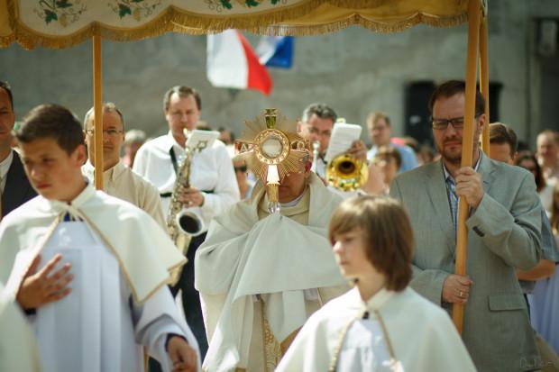 Podczas procesji Bożego Ciała ksiądz niesie pod baldachimem Najświętszy Sakrament w monstrancji.