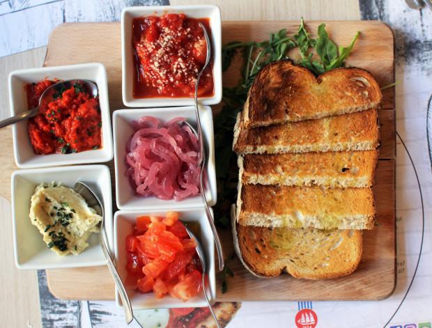 La bruschetta Romana - zestaw składający się z pomidorów z bazylią, fasoli z paskami słoniny, flaczków po rzymsku, grillowanych papryk, kremu z karczochów oraz grzanek z chleba z oliwą.
