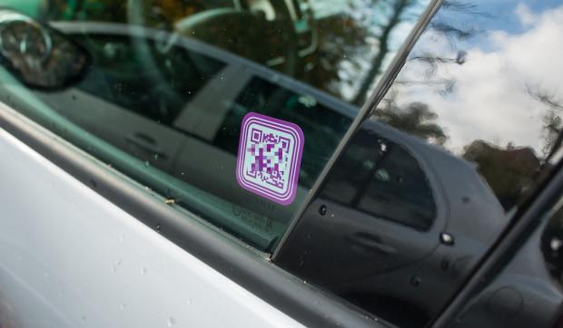 Kod QR umieszczony na szybie samochodu, niezbędny do jego otwarcia telefonem komórkowym.