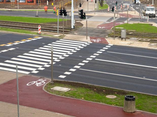 Rozwiązania rowerowe wokół Forum Gdańsk. Auta krótko i optymalnie, rowerowerzyści i piesiradosnym slalomem-gigantem w dyscyplinie pomiędzysłupkowej. Kosz na śmieci okrasza dekoracyjnie drogędla rowerów koronując dzieło sztuk piękno-inżynierskich. Na plus dobra nawierzchnia, niwelacja, szerokość. Oznakowanie w większości na pierwszy rzut oka poprawnie.