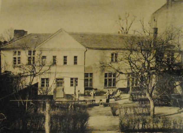 Dawny zajazd (widoczny od tyłu) w 1941 r., kiedy pełnił funkcję centrum szkolenia pomocniczek łączności Wehrmachtu. Widać zakwaterowane w ośrodku dziewczęta odpoczywające w ogrodzie (źródło: Soldat im Weichselland... 1941, Juli).