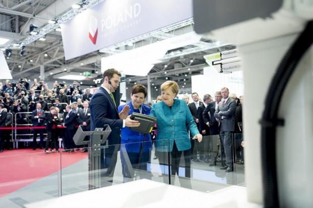 Była premier Beata Szydło i kanclerz Angela Merkel grają w kółko i krzyżyk z robotem kartezjańskim TMA Automation. Robota prezentuje Piotr Orlikowski, wiceprezes gdyńskiej firmy.
