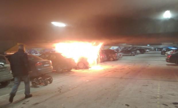 Płonące pojazdy na parkingu w centrum handlowym.