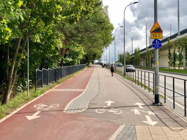 To jedno z ciekawszych, przemyślanych rozwiązań. Zjeżdżający szybko z góry rowerzyści prowadzeni sąosobno, a podjeżdżający powoli pod górę - razem z pieszymi, gdyżich prędkości sąwtedy zbliżone. Takie rozwiązanie należy stosowaćwszędzie tam, gdzie droga rowerowa / ciąg pieszo-rowerowy prowadzone są po znacznym nachyleniu. Oznakowanie jest klarowne i widoczne. Warto pochwalić.