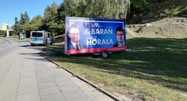 Kolejna przyczepa z plakatem wyborczym.