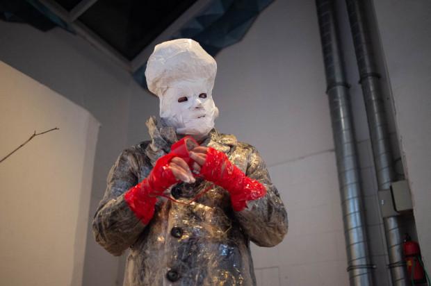 Kontrowersyjny artysta spektakl rozpoczął w papierowej masce i płaszczu pokrytym folią.