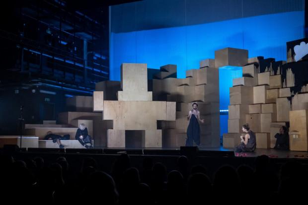 """Monumentalna kubistyczna konstrukcja z pudełek, przypominająca bloki skalne, to jeden z wielu zamierzonych dowcipów między """"wysokim"""" a """"niskim"""", jakie znajdziemy w spektaklu."""