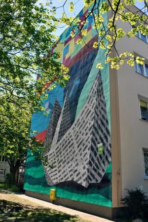 Na ścianie bloku przy al. Grunwaldzkiej 180 znajduje się kontenerowiec, przed którym płynie statek z papieru.