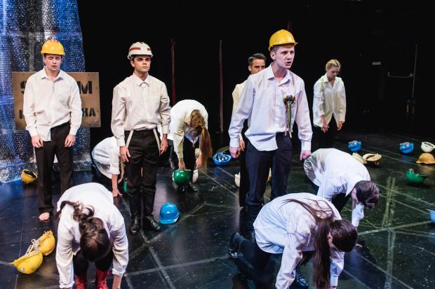 """W pewnym momencie konwencja spektaklu zostaje przełamana i przenosimy się w realia robotnicze, a adepci SWA śpiewają m.in. """"Mury"""" Jacka Kaczmarskiego."""