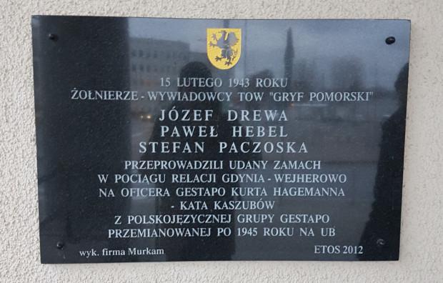 """Tablica upamiętniająca udany zamach na oficera gestapo, umieszczona na budynku dworca Gdynia Główna. Tu także pojawia się informacja o """"polskojęzycznej grupie gestapo"""", której istnienia nie potwierdzają żadne znane historykom dowody."""