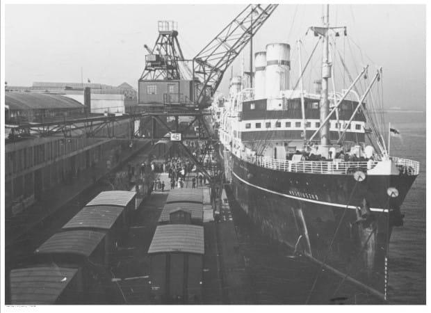 """Statek pasażerski s/s """"Kościuszko"""" widoczny od strony dziobu podczas przeładunku w porcie w Gdyni. Widoczne portowe urządzenia przeładunkowe oraz wagony kolejowe."""