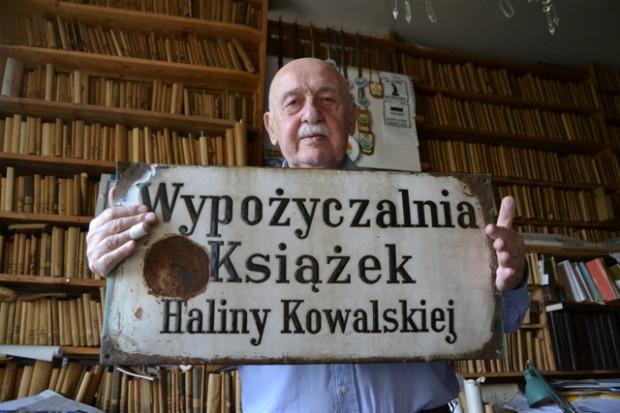 Architekt Janusz Kowalski na tle pozostałości księgozbioru swoich rodziców i z pamiątkowym, metalowym szyldem dawnej wypożyczalni książek.