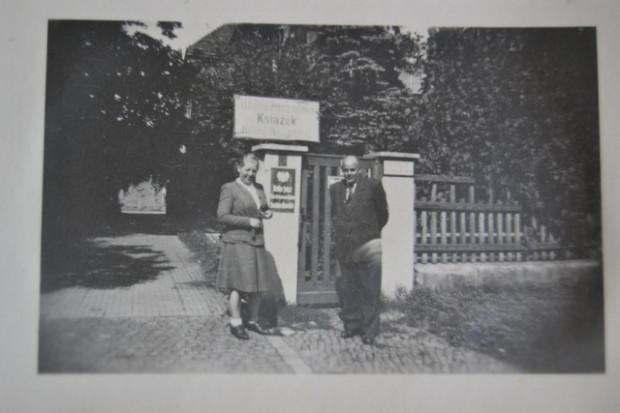 Halina i Stanisław Kowalscy przez willą, w której mieściła się kancelaria notarialna i wypożyczalnia książek. Na furtce widać szyld wypożyczalni książek. Fotografia ze zbiorów Janusza Kowalskiego