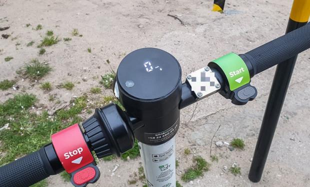 Kierownica hulajnogi z manetką hamulca (stop), wyświetlaczem oraz manetką przyspieszenia (start).