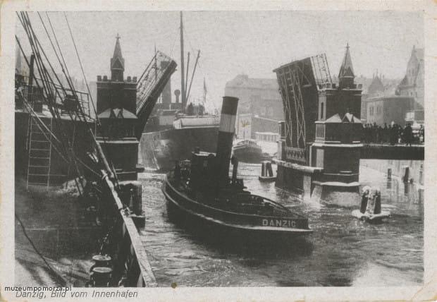Na zdjęciu widoczny jest zwodzony, dwuklapowy Most Krowi. Dzięki odpowiedniemu mechanizmowi możliwe było podnoszenie przęseł mostu, co umożliwiało żeglugę Starą Motławą nawet dużym jednostkom pływającym.