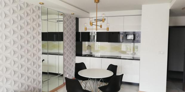 Umieszczenie tafli lustra w niewielkiej kuchni pozwala  optycznie ją modelować - powiększyć, poszerzyć lub podwyższyć.
